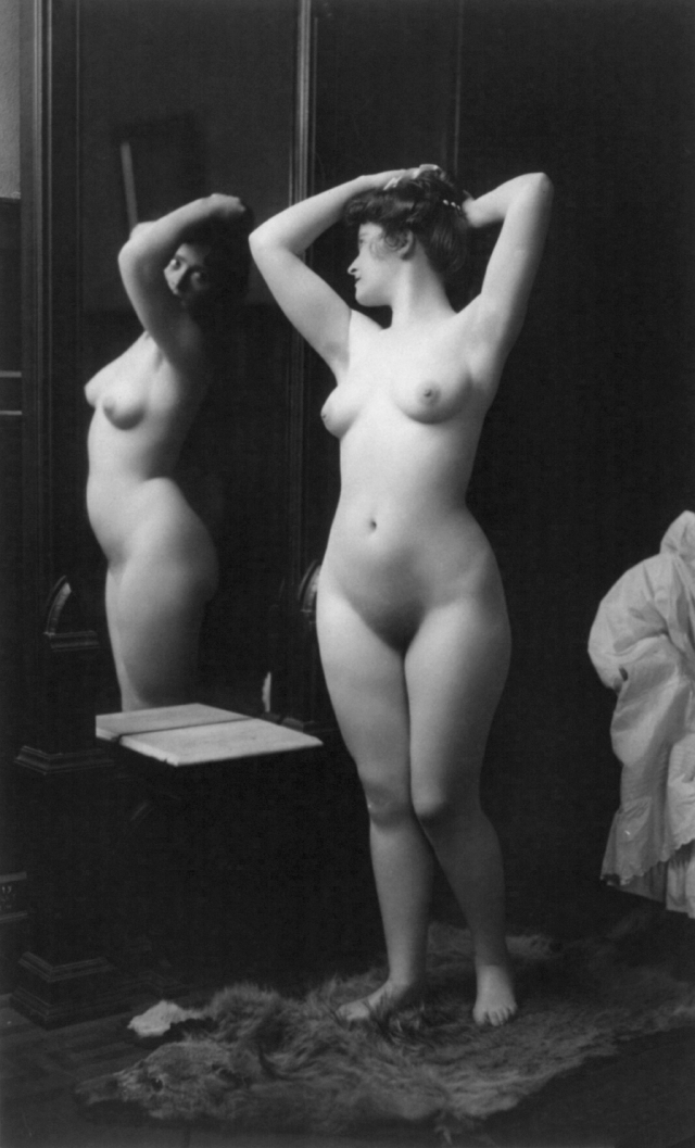 Vintage-nude-photo-of-a-naked-woman-looking-at-herself-in-a-mirror.png